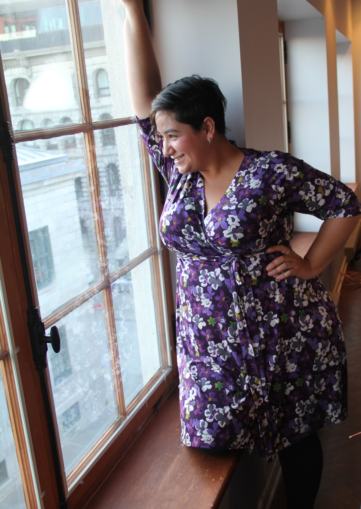Author in a floral print dress looking out a window